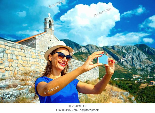 Girl in the hat making selfie by the smartphone on the background of the church in the mountains, Montenegro, Balkans
