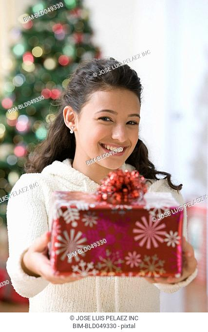 Hispanic teenaged girl holding out gift