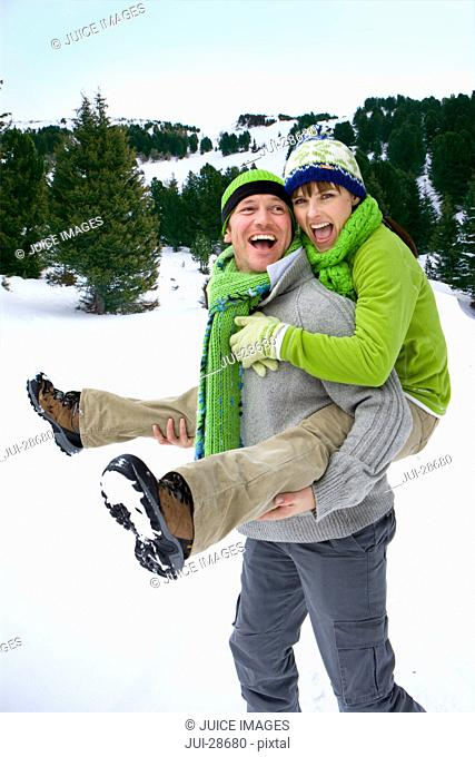 Smiling man giving wife a piggyback ride in snowy woods