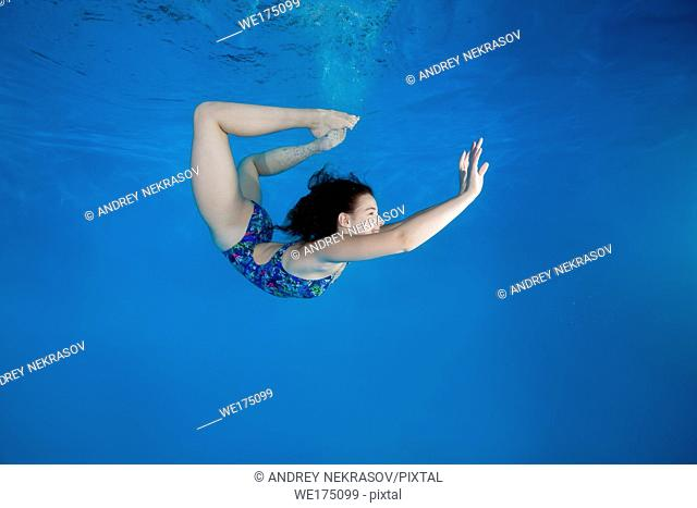 Girl curled into a wheel under water in the pool. Underwater acrobatics