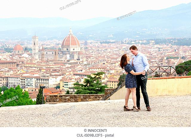Young couple dancing, Santa Maria del Fiore in background, Florence, Toscana, Italy