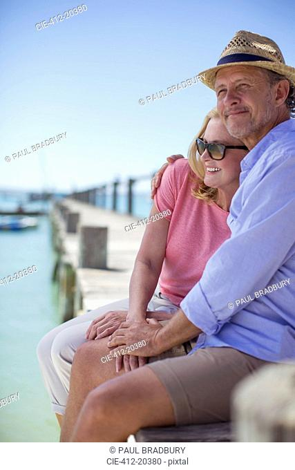 Couple sitting on edge of wooden dock together