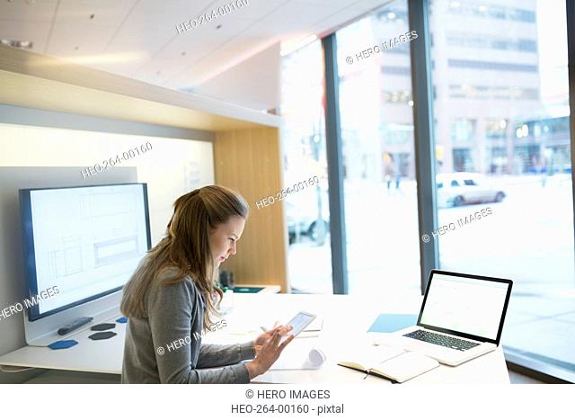 Young businesswoman using digital tablet in urban office