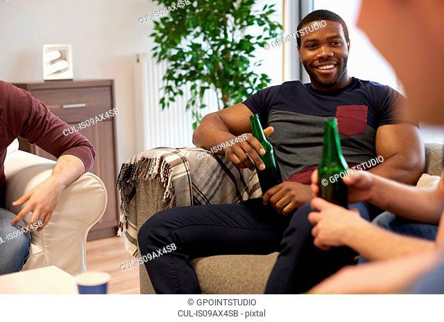 Group of men sitting in lounge holding beer bottles smiling