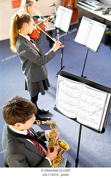 Middle school students playing saxophone and violin at sheet music in music class