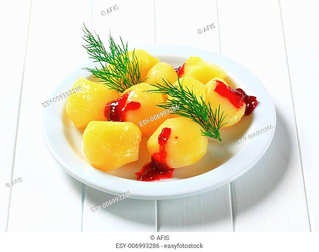 Cooked potatoes with dill and cranberry sauce
