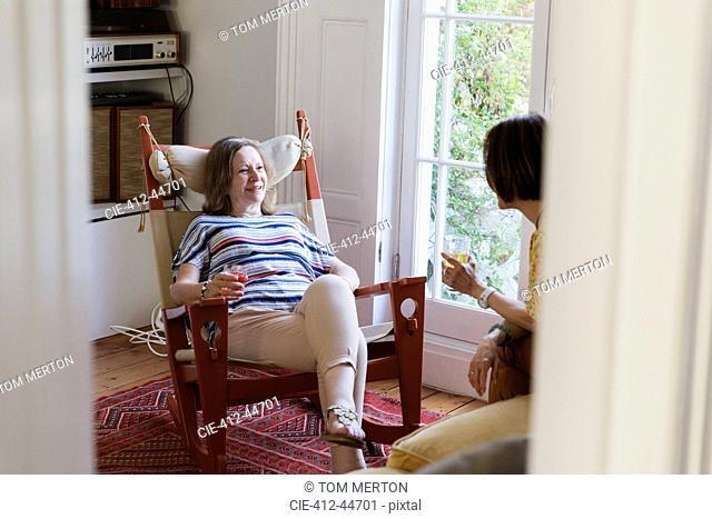 Senior women friends talking in living room