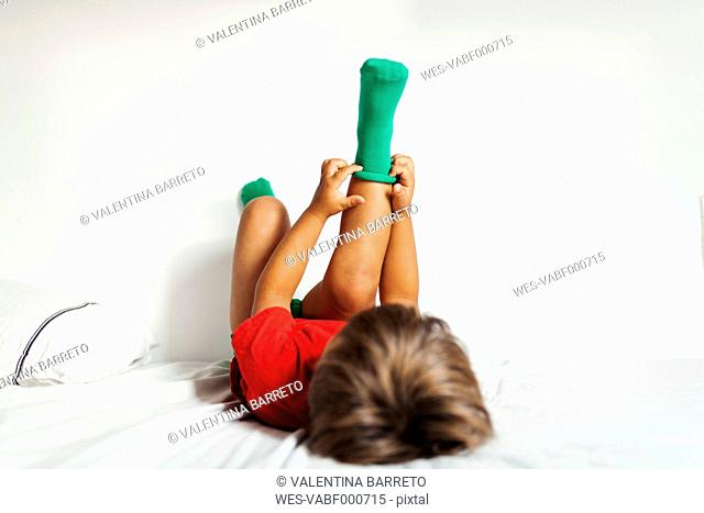 Back view of little boy lying on bed putting on his green socks