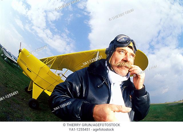 French pilot scratching his mustaches front of his biplane