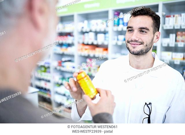 Pharmacist giving pill box to customer in pharmacy
