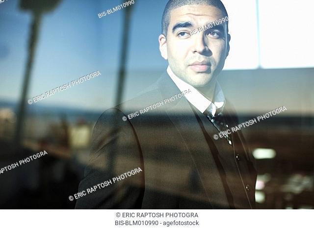 Mixed race businessman looking through window