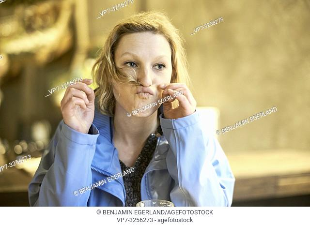 Young funny woman alone in cafe, hairs between nose and lips, Munich, Germany