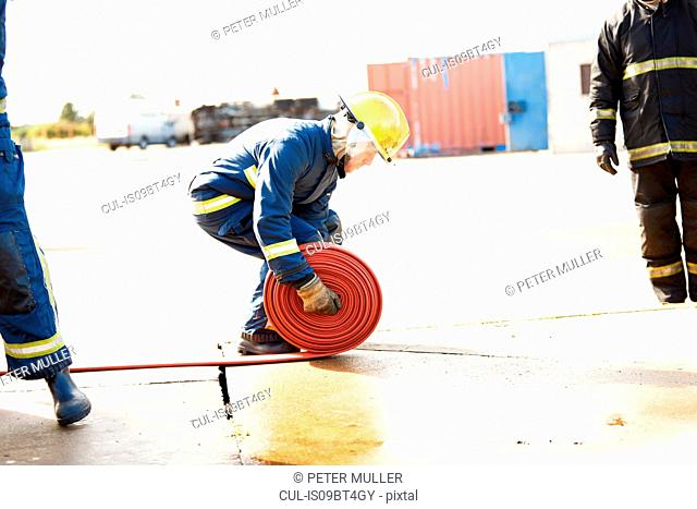 Firemen training, fireman unrolling fire hose at training facility