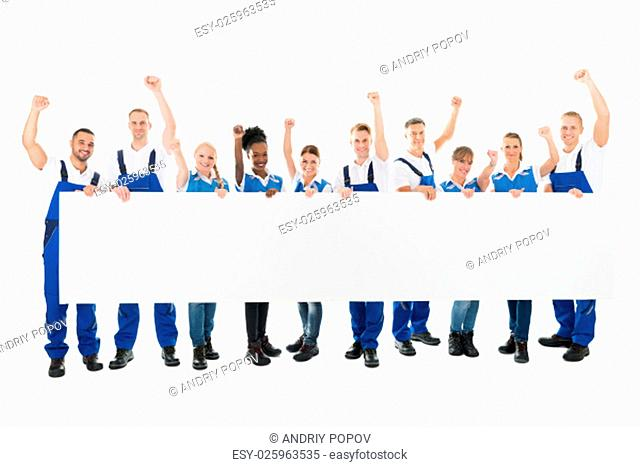 Full length portrait of happy janitors with arms raised holding blank billboard against white background