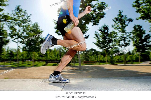 close up athletic legs of young man holding isotonic energy drink while running in city park with trees on the background on summer training session fitness and...
