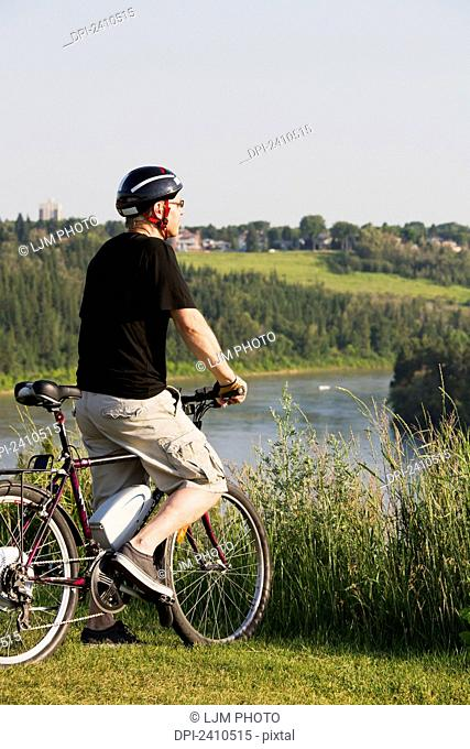 Man riding his electric bicycle with Edmonton city skyline in the background; Edmonton, Alberta, Canada