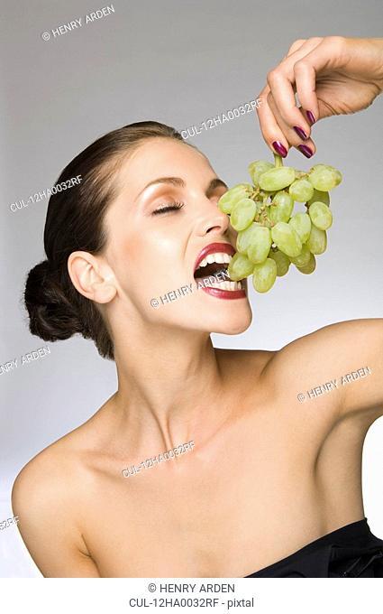female beauty eating grapes