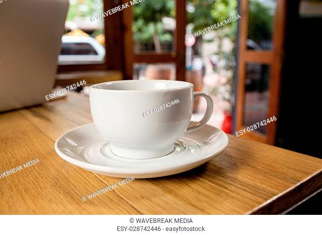 Close up of cup with saucer on wooden table