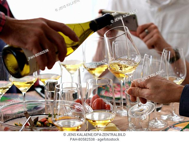 White wine is poured into glasses at a wine tasting in Berlin, Germany, 16 April 2016. Photo: JENS KALAENE/dpa | usage worldwide