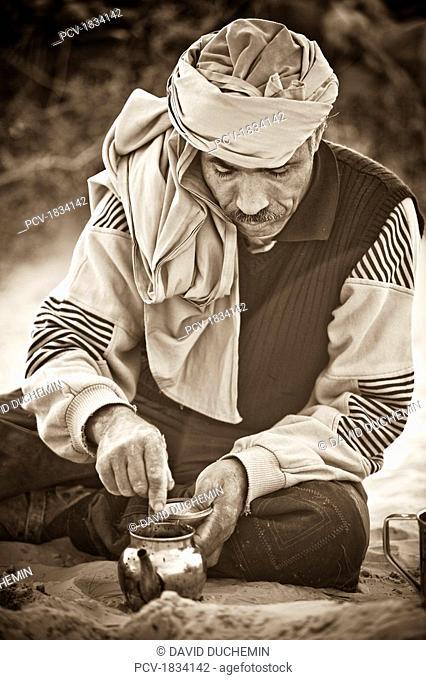 Douz, Sahara Desert, Tunisia, Man stirring small jug