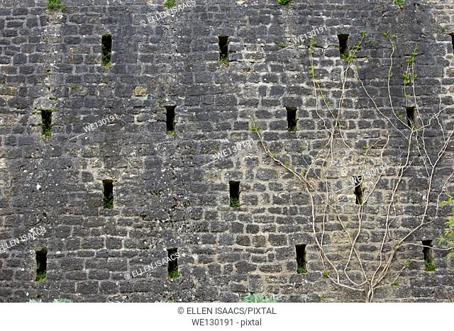 Regularly spaced holes in remains of a curtain wall protecting a medieval castle in Sarlat, France
