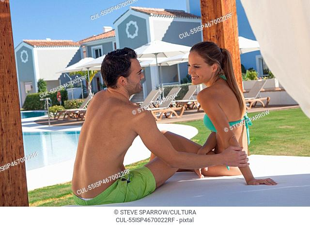 Young couple sitting on sunlounger at holiday resort