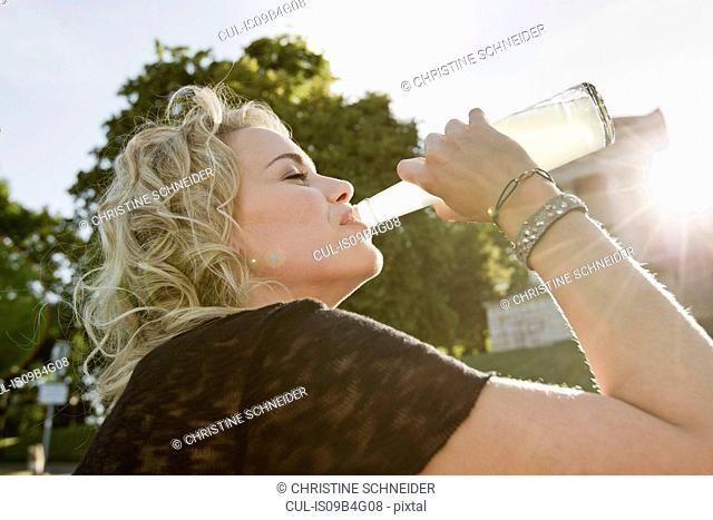 Mid adult woman in sunlit park drinking lemonade