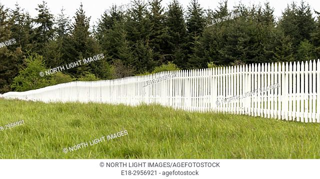 USA, WA, San Juan Island. Long white picket fence on the grounds of the American Camp