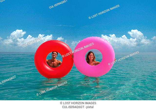 Couple looking through inflatable rings in sea