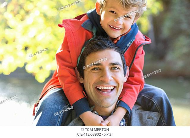Father carrying son on shoulders in park