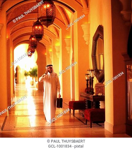 Arab man with briefcase using a cell phone