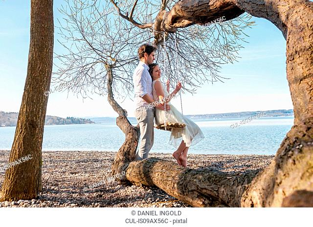 Side view of couple on tree swing by ocean