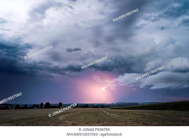 Lightning illuminated precipitation on the backside of a leaving supercell near Feuchtwangen, Baden-Wuerttemberg, Germany