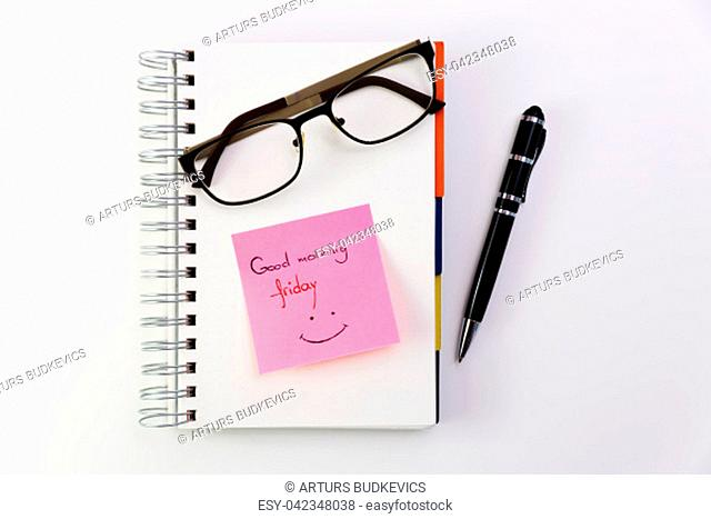 Good morning Friday, written on a post it glued to a notepad with glasses on top