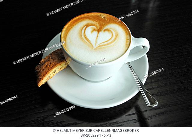 Cup of cappuccino decorated with a heart, and a biscotti on a black table