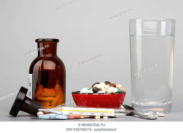 Various colored pills,medical bottle an glass of water