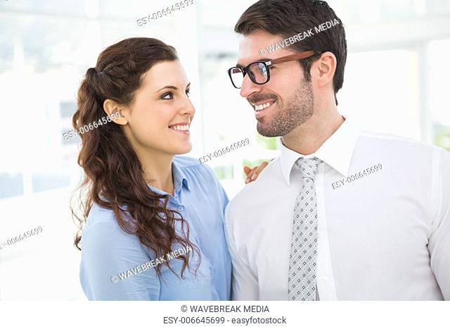 Smiling business colleagues looking each other