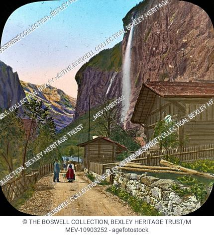 Coloured lantern slide of a view through the town of Lauterbrunnen. In the background is the Staubbach Falls. The waterfall drops about 300 metres from a...