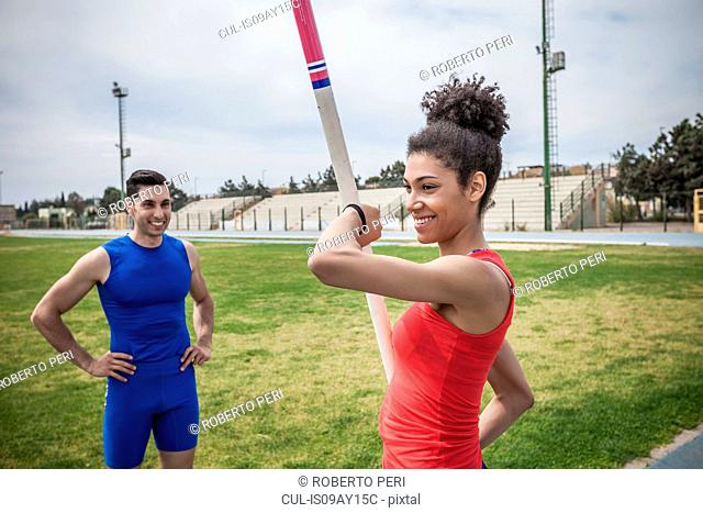 Instructor advising young female pole vaulter at sport facility
