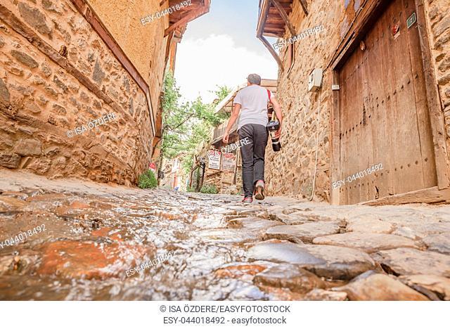Unidentified man walks at street of Cumalikizik village,a popular destination for Tourists and locals in Bursa,Turkey. 20 May 2018