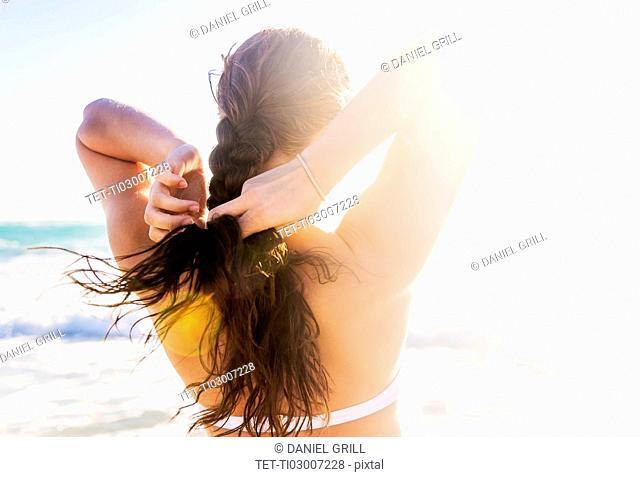 Woman braiding her hair on beach
