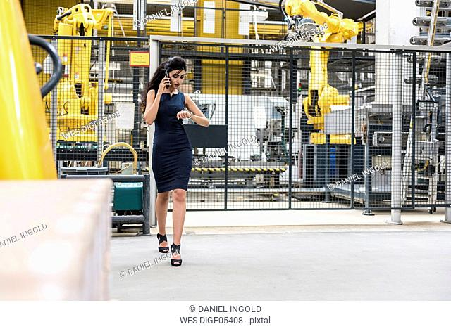 Woman on the phone walking in factory shop floor with industrial robot checking the time
