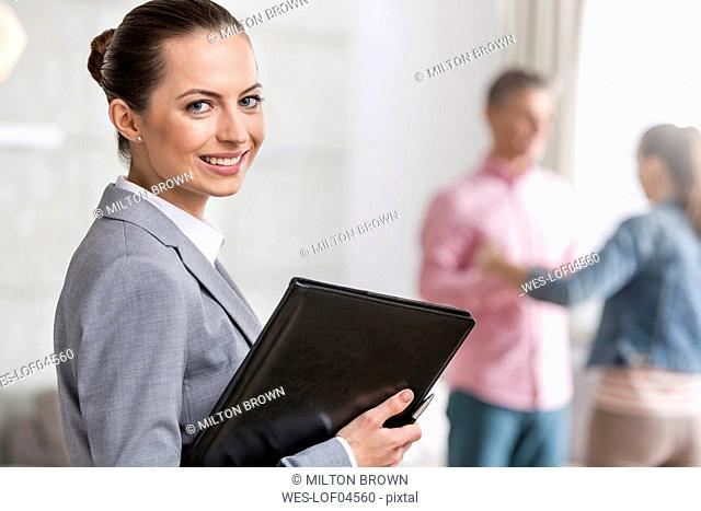 Portrait of smiling businesswoman and couple in background