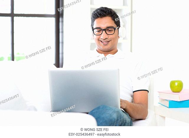 Indian guy listening to music with headset and laptop computer at home. Asian man using internet indoor, relaxed and sitting on sofa