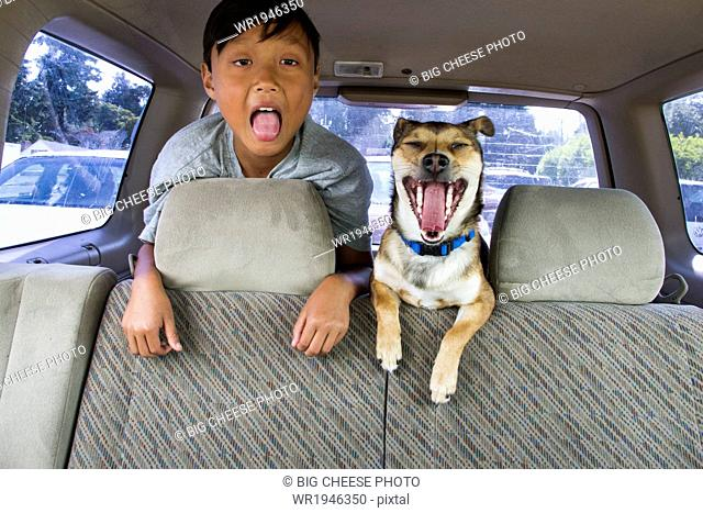 Child and his dog with their mouths open in the backseat of a car
