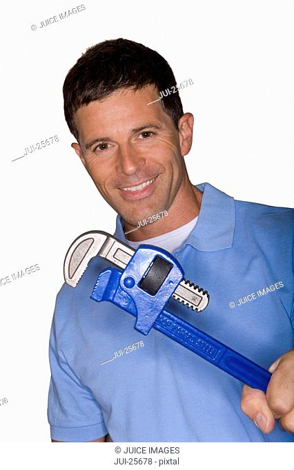 Smiling plumber holding large wrench