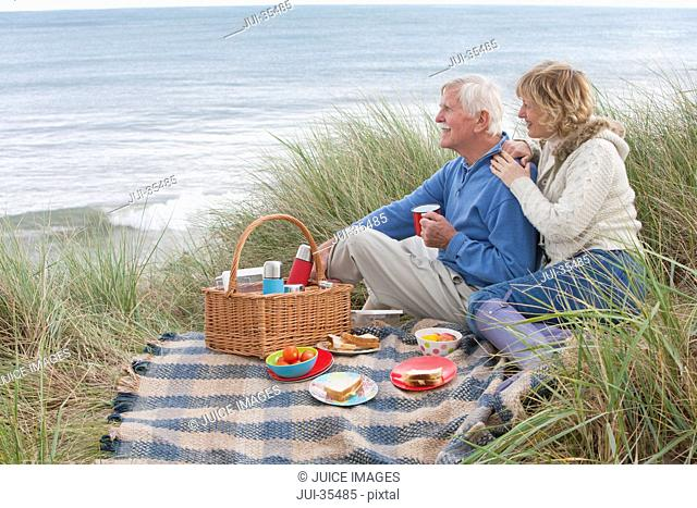 Mature Couple Enjoying Picnic In Sand Dunes