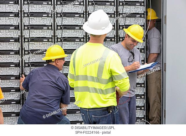 Engineers connecting backup batteries