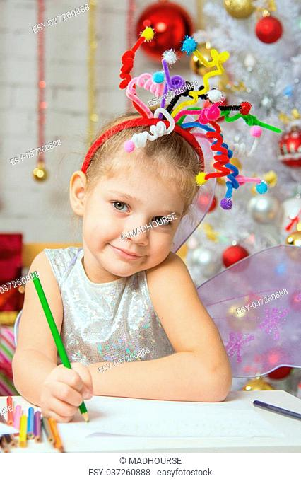 Girl with a toy fireworks on her head sitting at the table and draws a congratulatory New Years card
