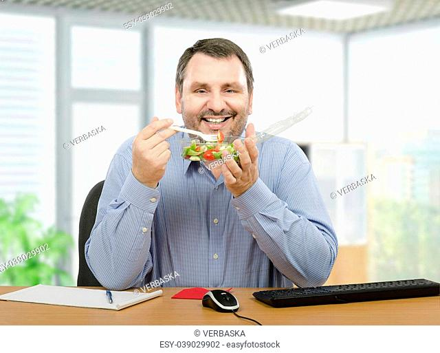 Middle-aged bearded managerial accountant is enjoying takeaway vegetable salad in plastic transparent container for lunch break. Horizontal portrait